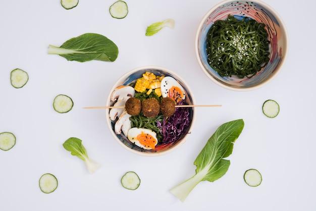 De kom van zeewiersalade met ramen traditioneel aziatisch die voedsel met komkommerplakken en blad op witte achtergrond wordt verfraaid