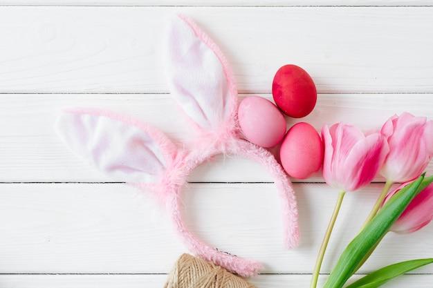 De konijntjesoren met tulpen en gekleurde eieren op houten vlakte als achtergrond lagen