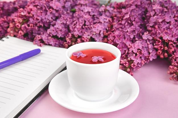De kop thee en de takken van de lente bloeien boeket bloeiende sering op purpere lijst.
