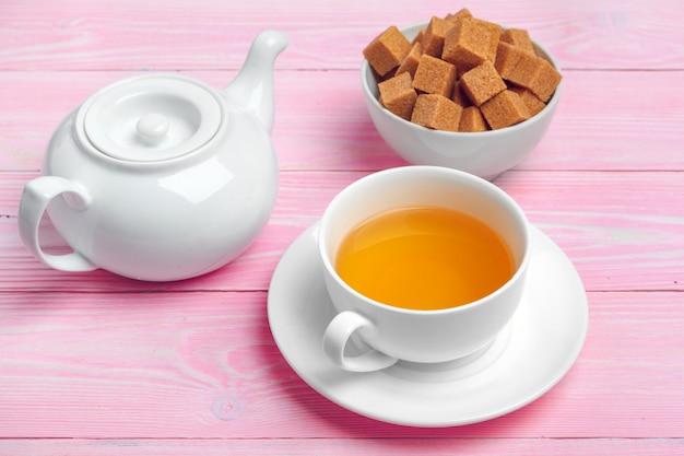 De kop thee met suikerkubussen en bloemtakken op houten lijst sluit omhoog