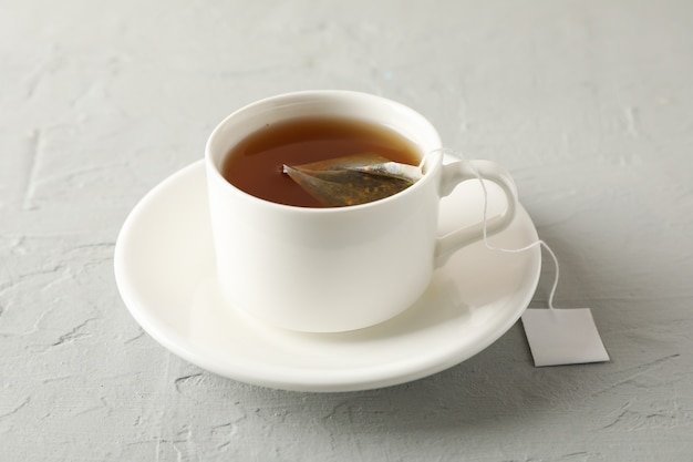 De kop thee met theezakje op grijs, sluit omhoog