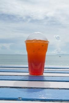 De kop van de ijsthee op witte lijst die op houten lijst in het strand wordt geplaatst