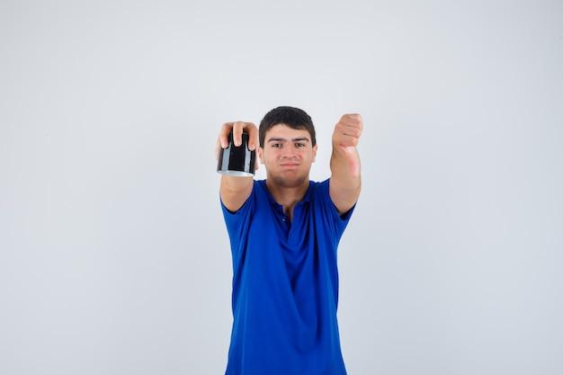 De kop van de jonge jongensholding, die duim in blauw t-shirt toont en zelfverzekerd kijkt, vooraanzicht.