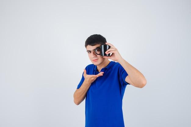 De kop van de jonge jongensholding, hand uitrekken als iets in blauw t-shirt vasthouden en ernstig, vooraanzicht kijken.