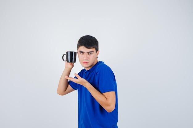 De kop van de jonge jongensholding, hand uitrekt zoals het voorstellen in blauw t-shirt en ernstig kijkt. vooraanzicht.