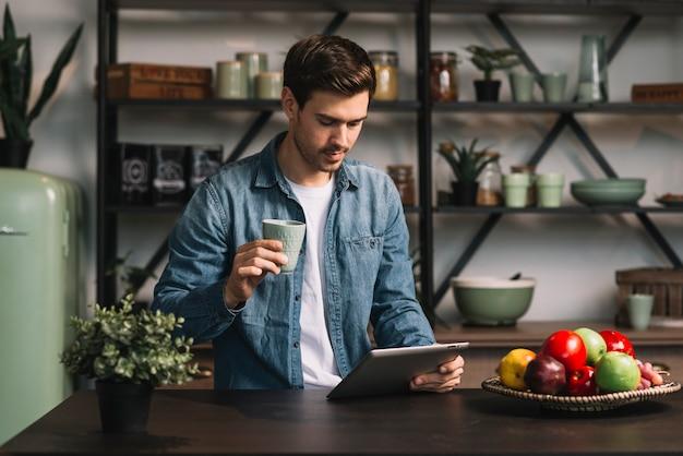De kop van de jonge mensenholding van koffie die digitale tablet bekijken