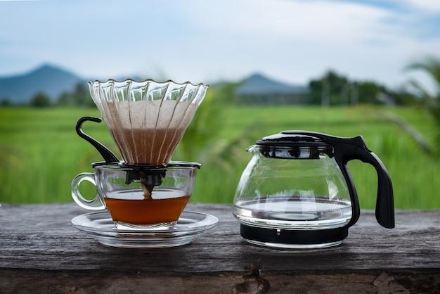 De kop van het koffieglas en waterpot op de houten lijst bij blauwe hemel