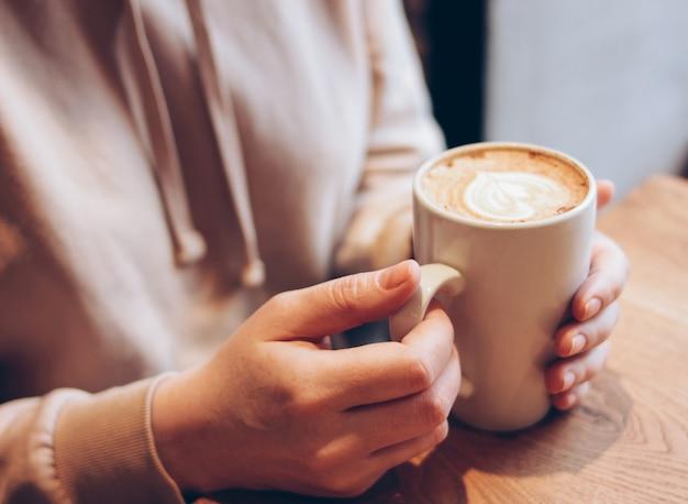 De kop van koffiecappuccino in vrouwelijke handen bij koffie, sluit omhoog