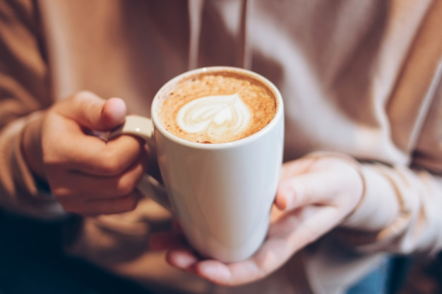 De kop van koffiecappuccino met schuimhart in vrouwelijke handen bij koffie, sluit omhoog