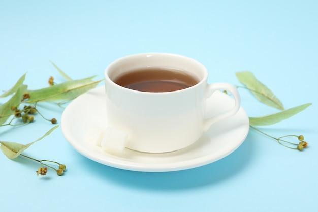 De kop van linde thee op blauw, sluit omhoog