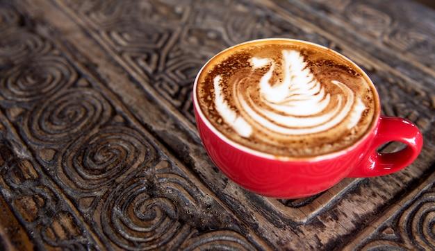 De kop van smakelijke cappuccino is op de houten geweven lijst