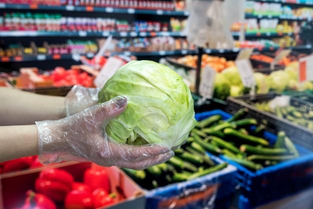 De koper in handschoenen kiest groenten tijdens een pandemie vanwege een nieuw gevaarlijk virus, coronavirus