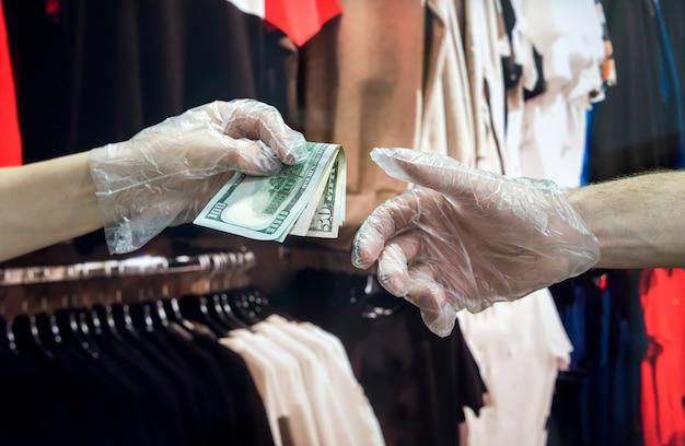 De koper in plastic handschoenen geeft de koper dollars voor de goederen in de kledingwinkel. hygiëne concept. pandemie als gevolg van een nieuw gevaarlijk virus. coronavirus