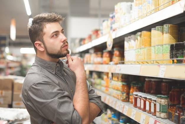De koper kiest ingeblikt voedsel in de winkel.