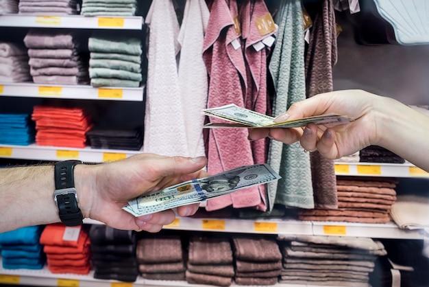 De koper koopt handdoeken voor het huis en geeft dollars aan de verkoper. winkelconcept