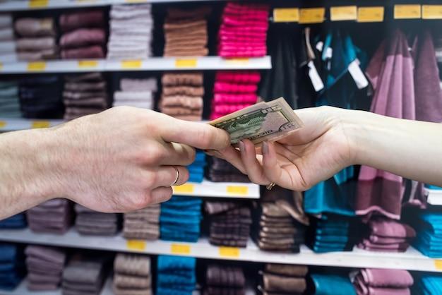 De koper koopt handdoeken voor het huis en geeft dollars aan de verkoper. winkelen concept
