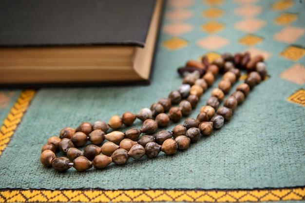 De koran en de oude rozenkrans op een groene mat