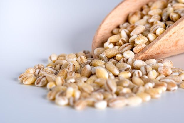 De korrels van de parelgort in houten lepel die op wit, gezond voedsel wordt geïsoleerd