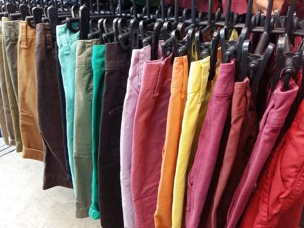 De korte broek van de kleurrijke man en van de vrouw op hangers
