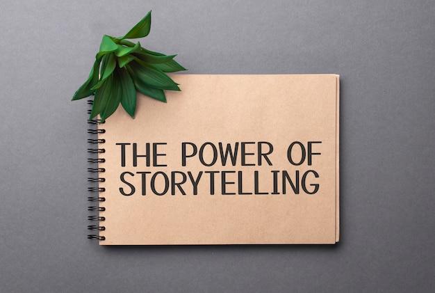 De kracht van storytelling-tekst op ambachtelijk gekleurd notitieblok en groene plant op de donkere achtergrond