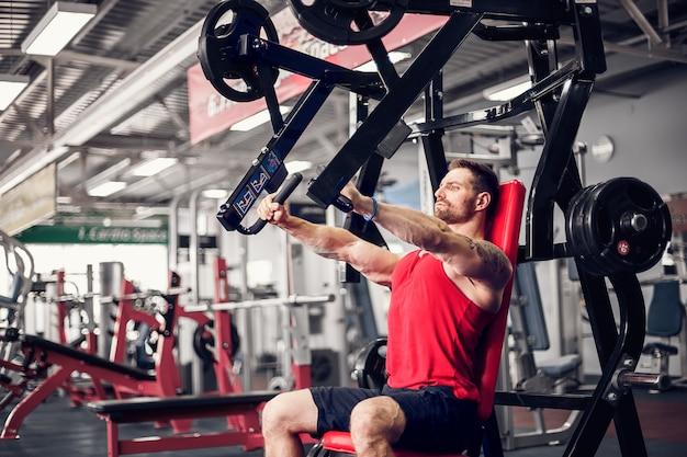 De krachtige atleet doet oefeningen op borstspieren