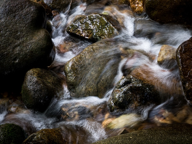 De kreekwaterval die van de bergstroom door rotsen in een tropisch bos vloeien.