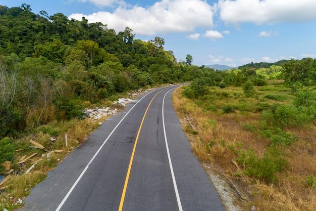 De kromme van de asfaltweg met gele lijn op wegbeeld door hoge de hoekmening van de hommelcamera.