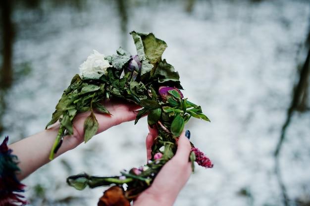 De kroon van de ggirlholding op handen bij sneeuwbos in de winterdag.