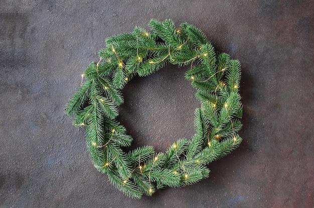 De kroon van de kerstdeur gemaakt van boom fir takken met lichten