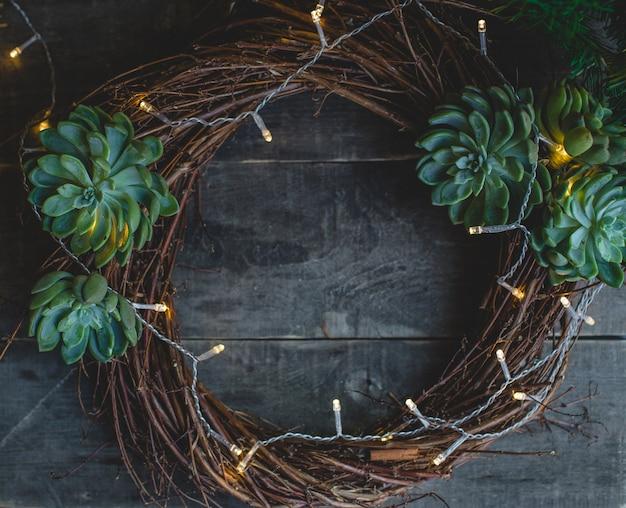 De kroon van de kerstdeur gemaakt van takken en suculentus.