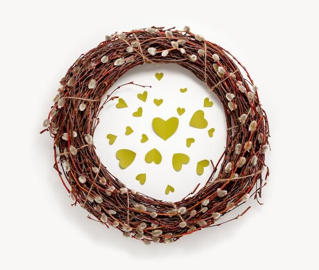 De kroon van de lentepasen, wilgentakken, groene harten, witte achtergrond. bovenaanzicht decoraties plat lag lente banner