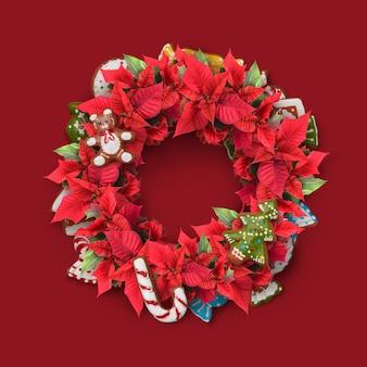 De kroon van het takje van kerstmis is versierd met snoep, rode bloemen, koekjes en groene bladeren.