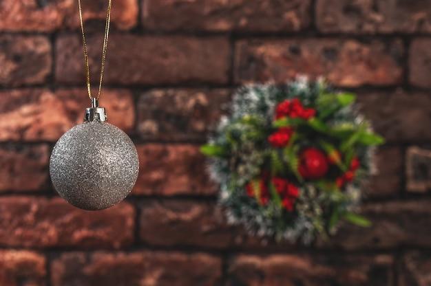 De kroon van kerstmis en kerstmis zilveren bal op rode bakstenen muur.