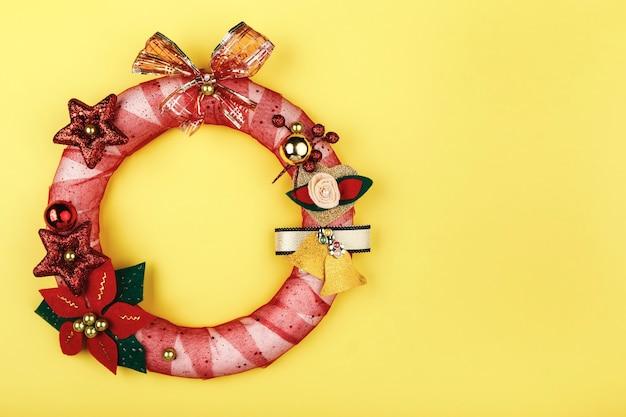 De kroon van kerstmis met handgemaakte decoraties op gele achtergrond