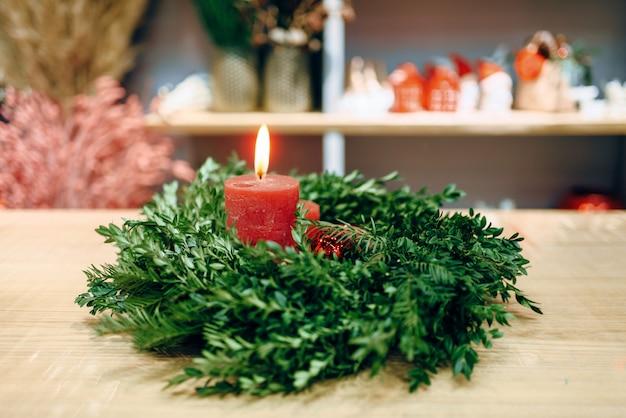 De kroon van kerstmis met rode brandende kaars close-up weergave, niemand. vakantiesymbool, de vertakking van de cirkelspar en kaarslicht, adventdecoratie, kerstmisviering