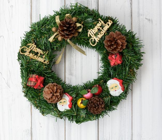 De kroon van kerstmis op witte houten deurdecoratie, plat leggen