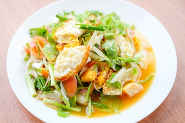 De kruidige salade met gebraden eieren (yam kai dao) dient op witte schotel die op bruine lijst wordt geplaatst - eigengemaakt voedselconcept.