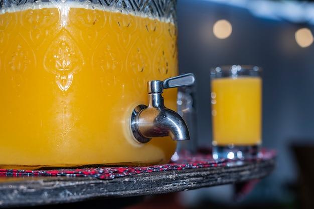 De kruik en het glas met tropisch sap van mango en passievrucht op de lijst, sluiten omhoog