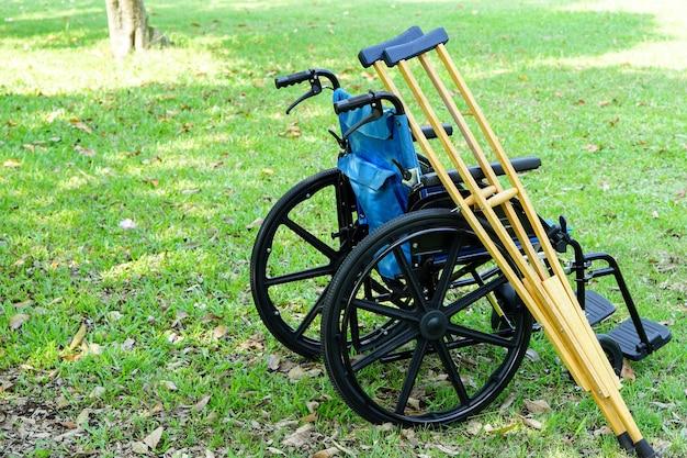 De krukken leunen tegen de rolstoel in het park of het gazon gezondheidszorg en medisch concept medical