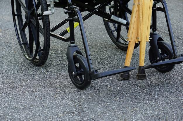 De krukken leunen tegen de rolstoel in open ruimtes of buiten gezondheidszorg en medisch concept