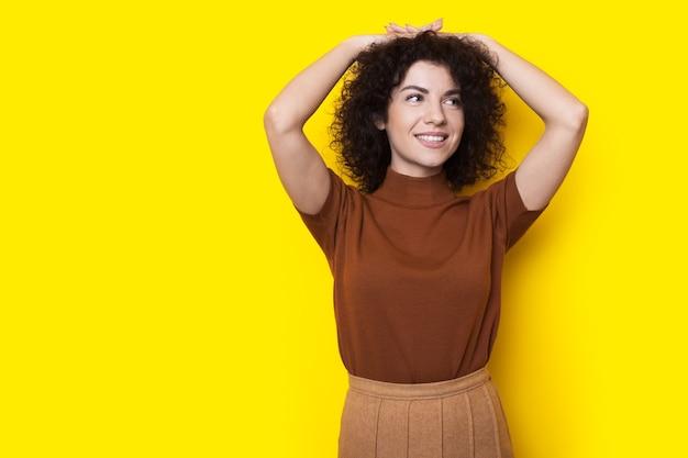 De krullende harige vrouw glimlacht wat betreft haar haar en stelt op een gele studiomuur met vrije ruimte