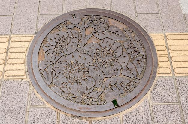 De kunst boven de afvoerkap op straat in fukuoka prefecture