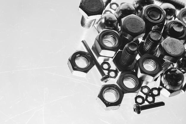 De kunst zwart-wit achtergrond van bouten en noten sluit omhoog in blauwe backlight. handvol bevestigingsmiddelen in macro. kopieer ruimte.