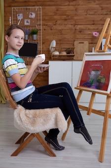 De kunstenaar het meisje drinkt thee tijdens het tekenen