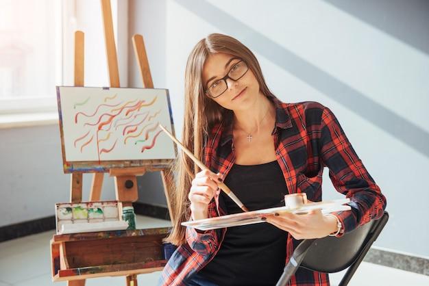 De kunstenaar pretty pretty girl schildert op canvas op de ezel.