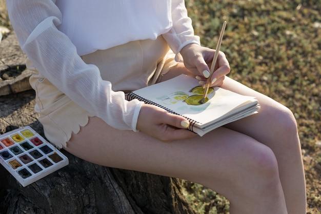 De kunstenaar schildert een foto buiten in de vroege zonnige ochtend.