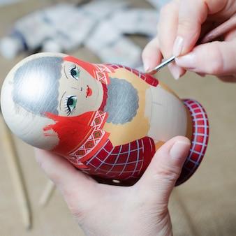 De kunstenaar tekent een pop-matryoshka. vrouwelijke handen met een borstelclose-up.