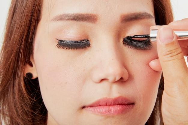 De kunstenaar van de make-up lijmt wimpers op cliënt