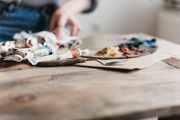 De kunstenaar werkt met een palet van verven