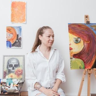 De kunstenaarszitting van de vrouw in workshop